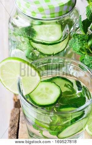 Glass and jar mug with infused detox cucumber water with lime and fresh mint close up cleansing spring