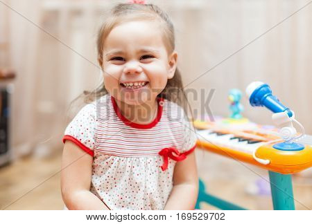 Child little girl playing on a toy piano at home