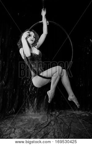 Girl Dancer Sitting On Round At Circus In The White Dust With Flour On A Black Background. Studio Sh