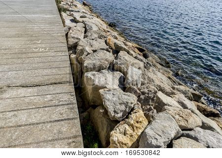 Breakwater by the Mediterranean sea on the island of Ibiza in Spain, holiday and summer scene
