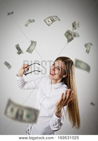 Rejoicing. Woman in white and falling dollar banknotes. Success currency and lottery concept.