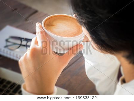 Hand on cup of coffee at work table stock photo