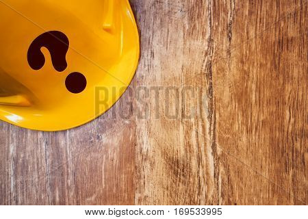 Protective yellow construction helmet with question mark on wooden table top view