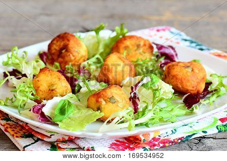Crispy fried mashed potato balls. Delicious fried balls made from mashed potatoes with pumpkin seeds served with salad leaves mix and basil on a plate. Closeup