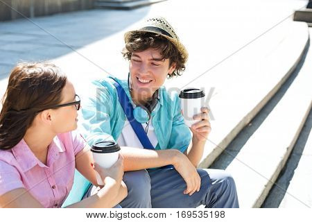 Happy friends holding disposable coffee cups while sitting on steps outdoors