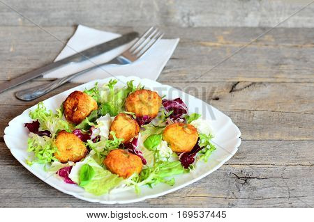 Crispy fried potato balls. Tasty fried mashed potato balls with pumpkin seeds garnished with fresh lettuce and basil on a plate. Cutlery, napkin on vintage wooden background with empty place for text