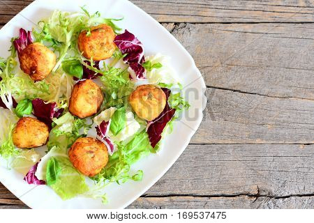 Fried potato balls recipe. Homemade fried mashed potato balls with pumpkin seeds served with fresh lettuce and basil. Wooden background with copy space for text. Top view