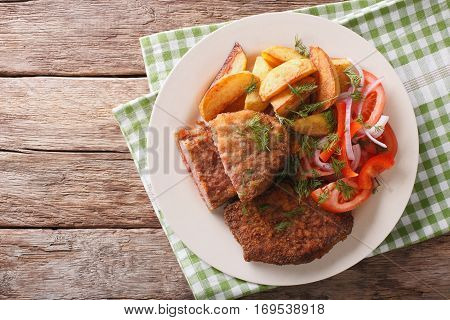 Veal Breaded Rump Steak And Garnished With Vegetables Close-up. Horizontal Top View