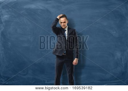 Businessman on blue chalkboard background holding one hand on his head in confusion. Business and success. Problems and solutions. Challenges.