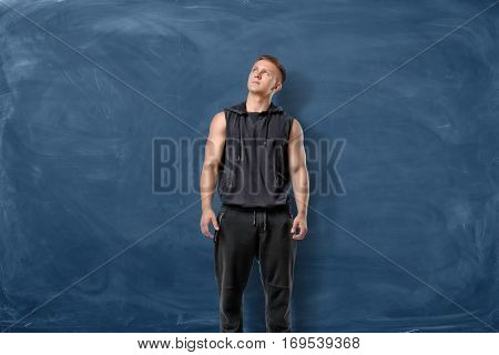 Muscular young man is standing and looking up on blue chalkboard background. Sport and healthy lifestyle. Keep fit. Athletic body