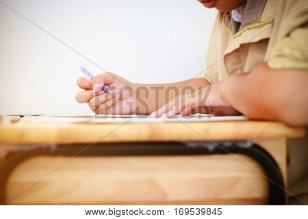 students writing on a paper for exams and admissions in high school with uniform Thailand : education concept