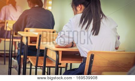 School students in uniform attending examination in a classroom in educational scholl: view of college people having exams in class room in seat rows