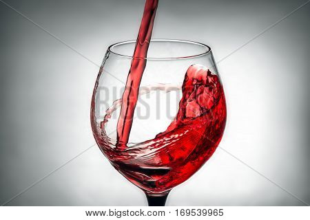 red wine pouring splash into glass on grey background