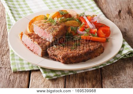 Veal Breaded Rump Steak And Garnished With Vegetables Close-up. Horizontal