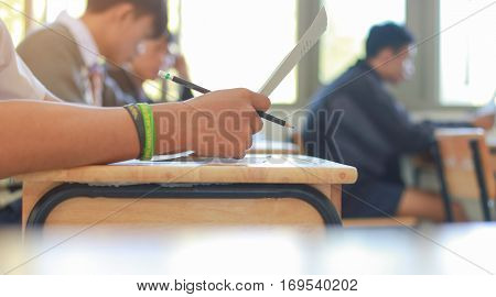 students writing test exam on paper for Admissions in high school with uniform student in School classroom of Thailand exam student background and education concept
