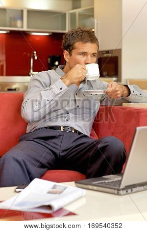 Young man drinking tea, sitting in sofa