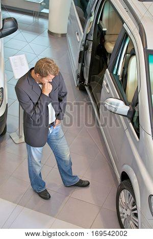 Young man examining new car at showroom