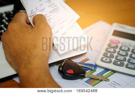 Concept,Slip in hand and car key with calculate income and expenses for the car.