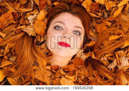 Nature concept. Beautiful girl between leaves. Autumn in the park. Young lady is enjoying good weather. Looking straigh ahead.