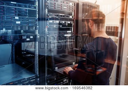 young it engeneer business man with thin modern aluminium laptop in network server room