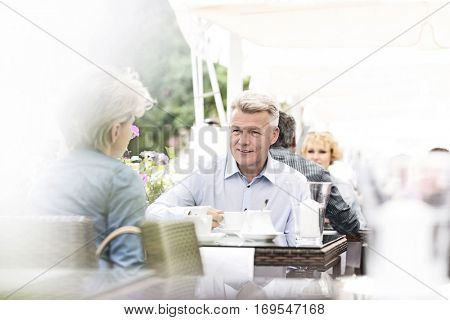 Middle-aged couple sitting at sidewalk cafe on sunny day