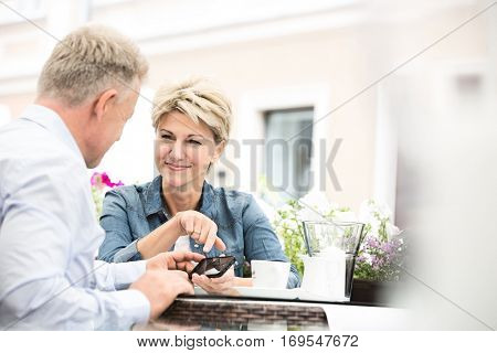 Happy middle-aged couple using cell phone at sidewalk cafe