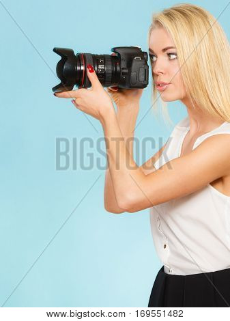 Photographer girl shooting images. Attractive blonde woman taking photos with camera on gray background