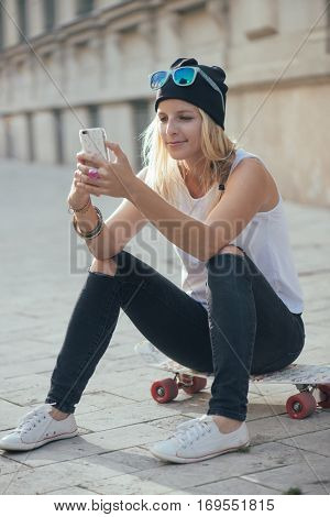 Cute blonde hipster woman posting to social media