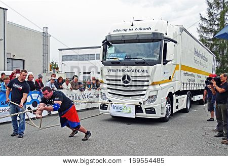 Chemnitz, Germany - October 4, 2015: A strong man pulling a 15 ton heavy truck with a rope in the final of FIROCON Truck Pull European Championships.