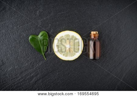 Homemade Essential Oil Concept. Bottle Essential Oil With Slice Lemon And Leaf In Heart Shape On Bla