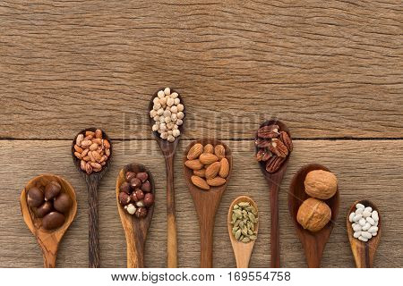 Different kind of beans and lentils in wooden spoon on wood background. mung bean groundnut walnuts macadamia almond soybean red kidney bean black bean sesame corn red bean and brown pinto beans
