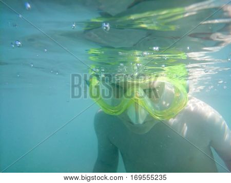 Kid in the mask for the snorkel surveys the bottom of the sea, underwater photography