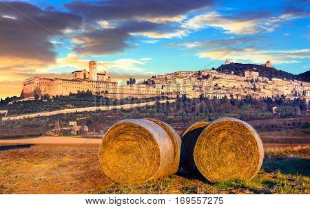 Italian countryside with hey rolls with view of impressive Assisi