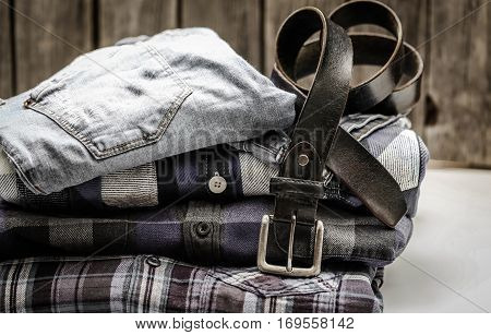 folded men's shirt in the box and the belt with jeans on wooden background , concept of style and fashion