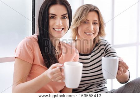 Join us. Two pretty energetic early risers holding up the cups with morning drinks while sitting by the window and enjoying their relaxing warm morning