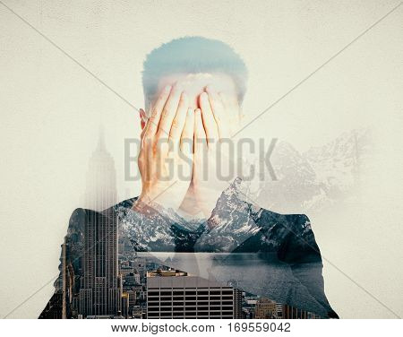 Man covering face with hands on abstract city and nature background with sunlight. Stress concept