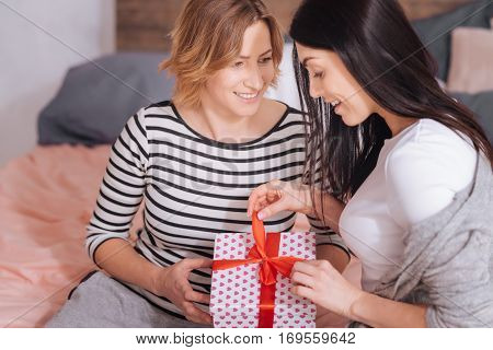 What is in there. Emotional charming graceful woman carefully unwrapping the gift her girlfriend presenting her while celebrating their anniversary during the weekend
