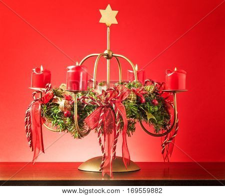 Vintage advent wreath with four burning candles and gold star on red background lights and decoration for christmas time