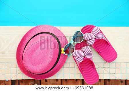 Pink hat, sunglasses and flip flops by   swimming pool