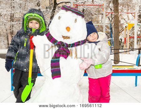 Two little fiends kids making a snowman playing and having fun with snow outdoor on cold day. Active outdoors leisure with children in winter