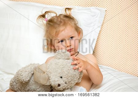Portrait of a sad girl child sitting on a bed in the bedroom with a toy. Kid waking up in bed unhappy. Time to bed