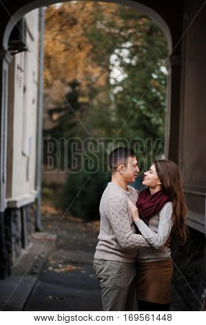 Young Couple Wearing On Tied Warm Sweaters Hugging In Love Under Arch At City In Autumn.