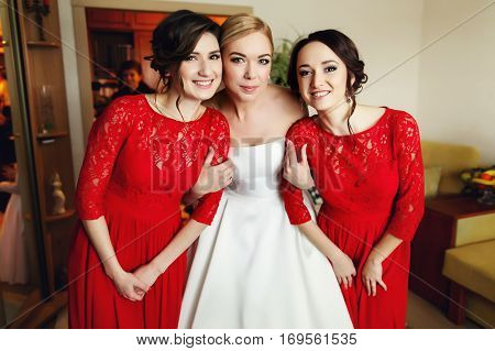 Bride Holds Hands Of Pretty Bridesmaids Dressed In Red