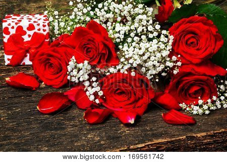 Red roses with gypsofilia seeds and a gift on wood