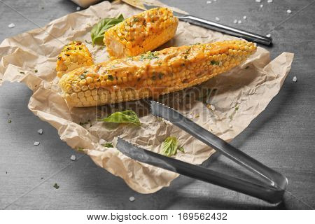Tasty grilled corncobs with basil, sauce and tongs on grey table, close up view