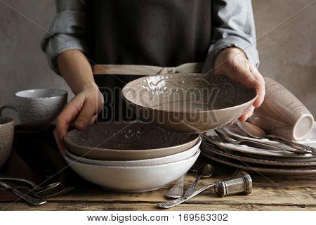 Female hands holding ceramic dishware, closeup