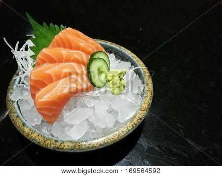 Special Deluxe salmon sashimi set on ice sever with wasabi and cucumber traditional Japanese food with space focus salmon with blur backgroup
