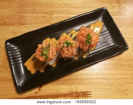 Fusion salmon sushi stuff with cucumber crab stick and mango Stylist food