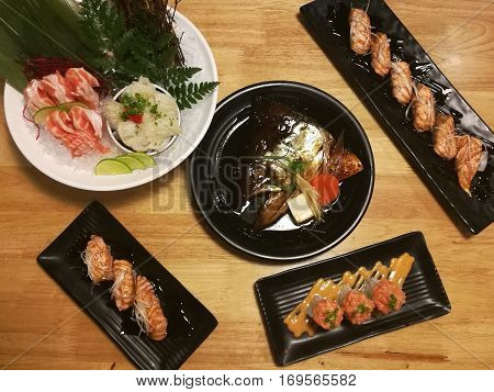 Special Japanese meal variety of sushi Salmon head Salmon sushi Salmon sashimi top view in the garden