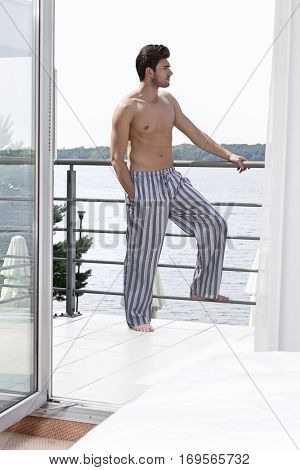 Full length of shirtless young man on hotel balcony looking away